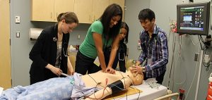 Students trying to resuscitate SimMan 3G in the Pritchard Simulation Centre.